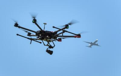 Imagen de archivo de un dron con un avión en el fondo, durante un...