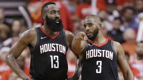 El guardia de Houston Rockets Chris Paul habla con James Harden durante...