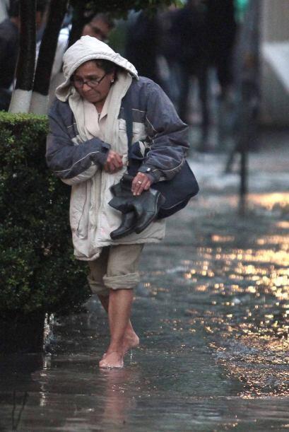 Esta mujer optó por quitarse sus botas para no mojarlas y caminó descalz...