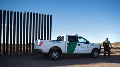 Un agente de la Patrulla Fronteriza observa un área cerca del mur...
