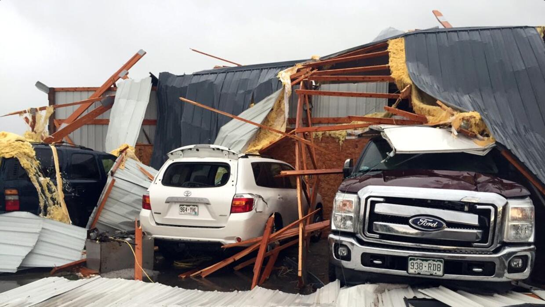 Escombros sobre varios autos vehículos dañados por el paso de un tornado...