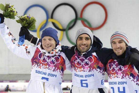 El esquiador francés Martin Fourcade (al centro) celebra en el po...