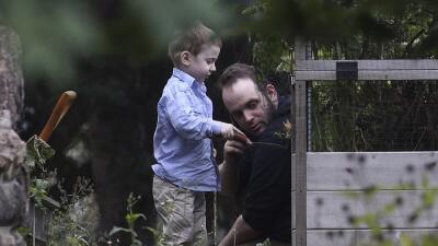 Johua Boyle y su hijo Jonah juegan en un jardín en su nueva resid...