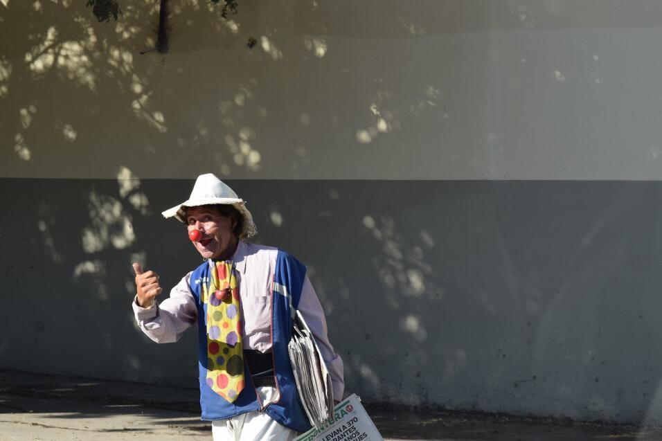 Un hombre disfrazado de payaso vende periódicos de Tijuana.