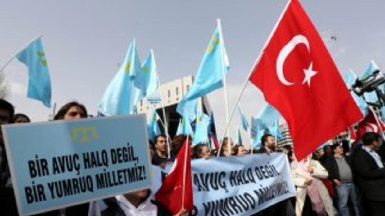 """Un hombre porta un cartel que dice """"No intervención militar en Crimea¨,..."""