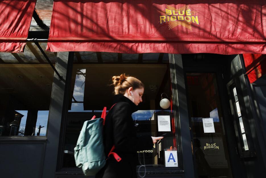 La gente camina frente al restaurante Blue Ribbon en Brooklyn. Negocios...