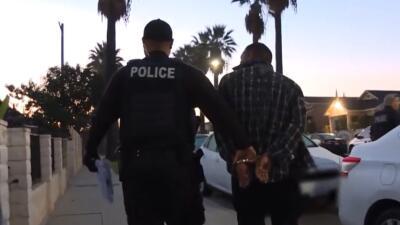 Un agente de ICE lleva a un inmigrante arrestado en Sur Los Ángeles dura...