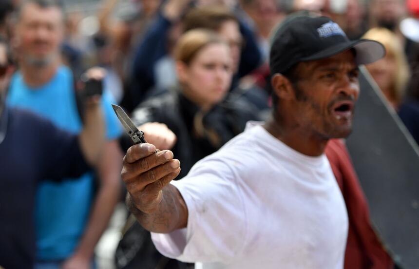 Un hombre muestra una navaja en medio de la multitud.
