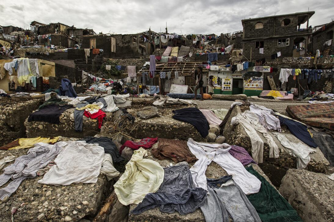 Wet clothes out to dry outside destroyed homes following the passage of...