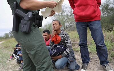 Un agente de la patrulla fronteriza chequea los certificados de nacimien...