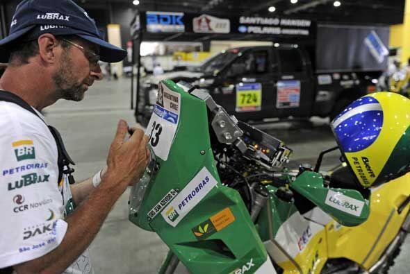 Un miembro del equipo KTM pone la identidicación en la moto del brasileñ...