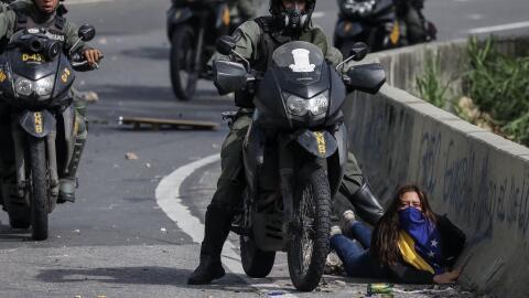 La chica en el suelo y el guardia nacional le pone la bota sobre la espalda