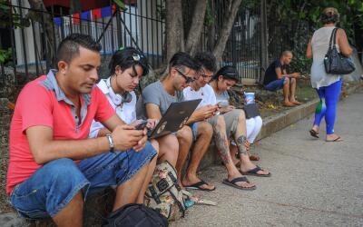 Decenas de cubanos usan el Wi-Fi al que tienen acceso en los espacios p&...