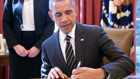 Obama signs an executive order in the White House in 2015.