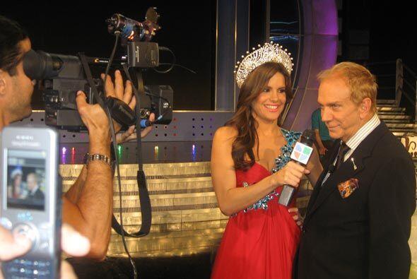 Haciéndo su labor como reportera, entrevistando al zar de la belleza.