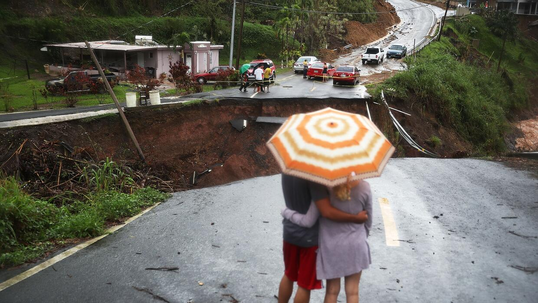 Residentes de Barranquitas esperan en una carretera derrumbada. 7 de oct...
