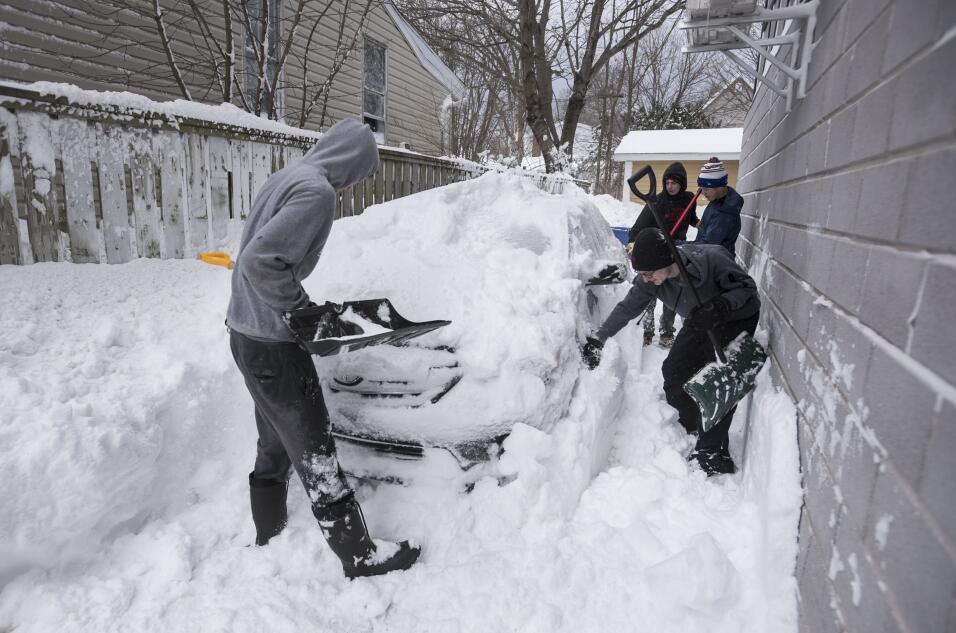 Consejos para manejar en nieve y hielo Boys dig a car out of the snow in...