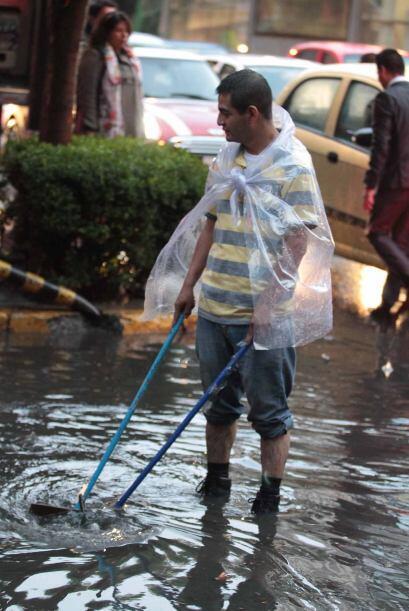 Un hombre trata de jalar el agua que inundó esta área del centro de la C...