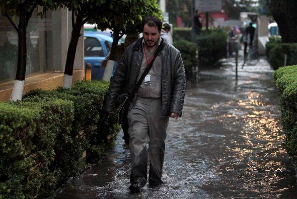 El agua manchó los pantalones de este hombre, que camina entre la inunda...