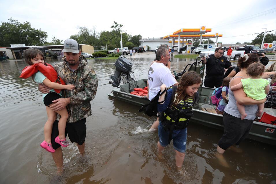 Vecinos utilizan sus botes personales para rescatar a los residentes de...