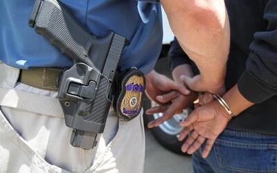 Un inmigrante indocumentado es arrestado y esposado por un agente de la...