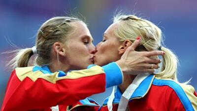Gushchina yRyzhova de Rusia se besaron en el podio al recibir su medall...