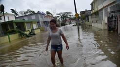 Una mujer camina por una calle inundada del barrio de Puerto Nuevo, en S...