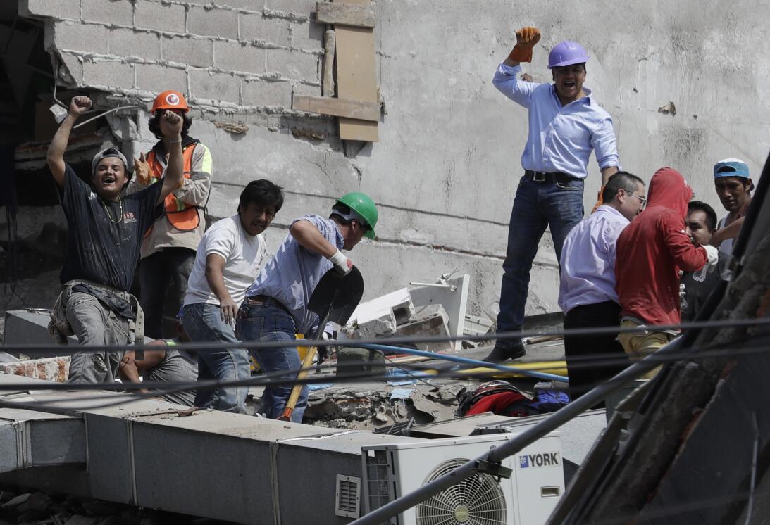 Voluntarios celebran brevemente el rescate de dos personas de un edifici...