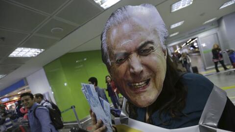 Un activista protesta con una máscara del presidente Michel Temer...