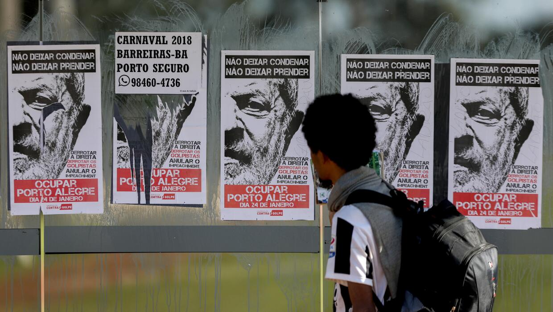 Un transeúnte mira los afiches en apoyo al expresidente Lula da Silva pe...