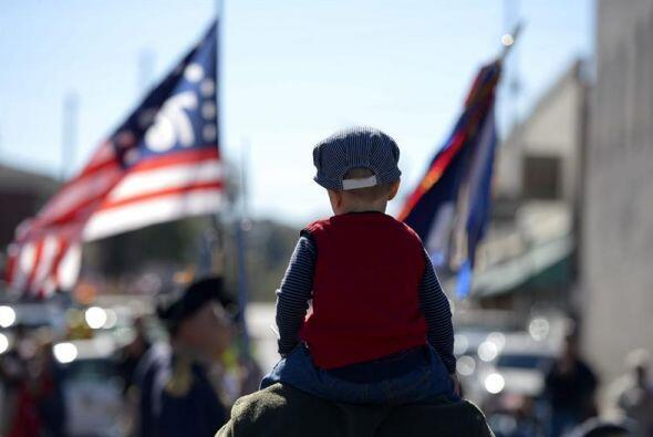 Un niño, subido sobre los hombros de su padre, observa el desfile celebr...