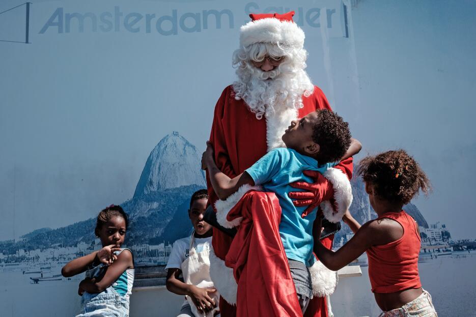 Y a Río de Janeiro también llegó Santa Claus, que saluda a unos niños en...