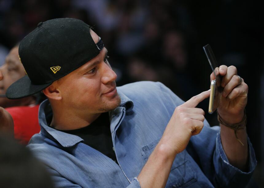 El actor Channing Tatum tomándose un selfie junto a su esposa en un jueg...