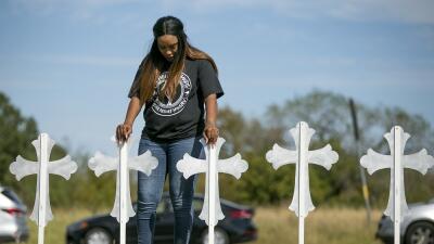 Una mujer reza frente a las 26 cruces levantadas en memoria de las vícti...