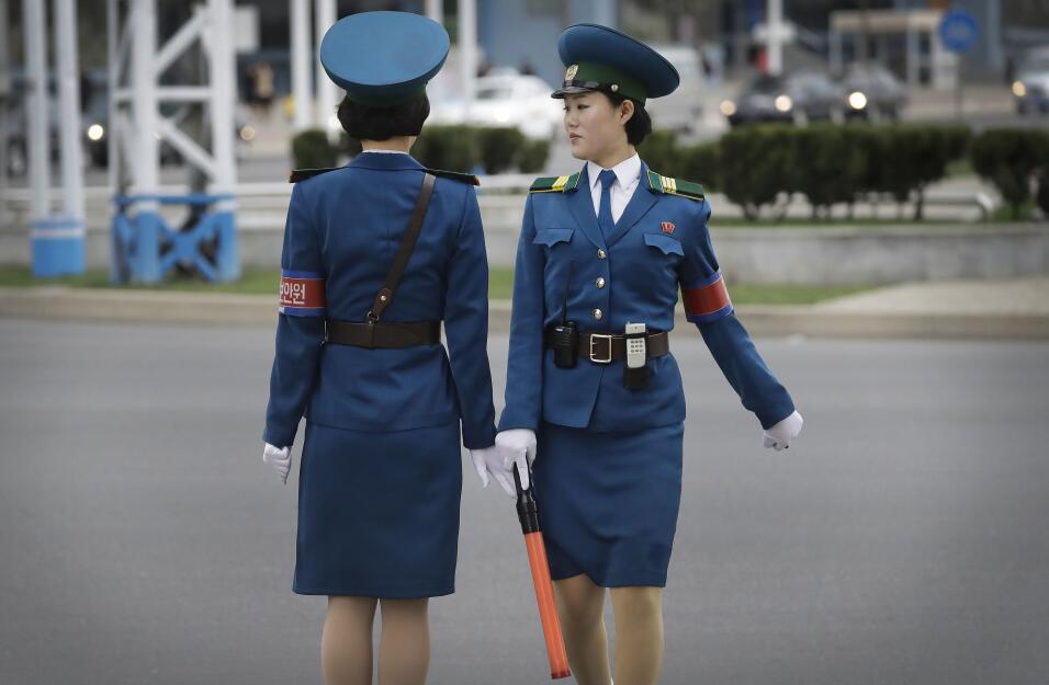 Se mueven con gracia, con entallados uniformes azules y tacones bajos en...