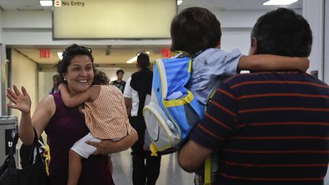 Elena Rojas, con su nieta Lilly, de tres años, en brazos, corre a...