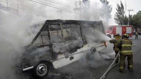 Los bomberos trabajan para extinguir un autobús en llamas luego de un ti...