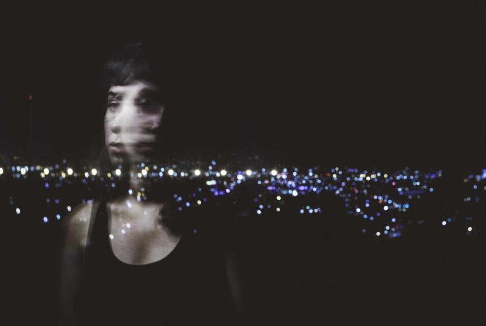 Una joven frente a las luces de la frontera.