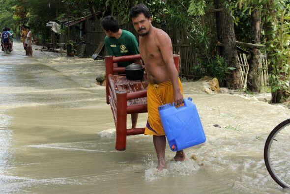 Este residente de Filipinas camina sobre las inundaciones por el paso de...