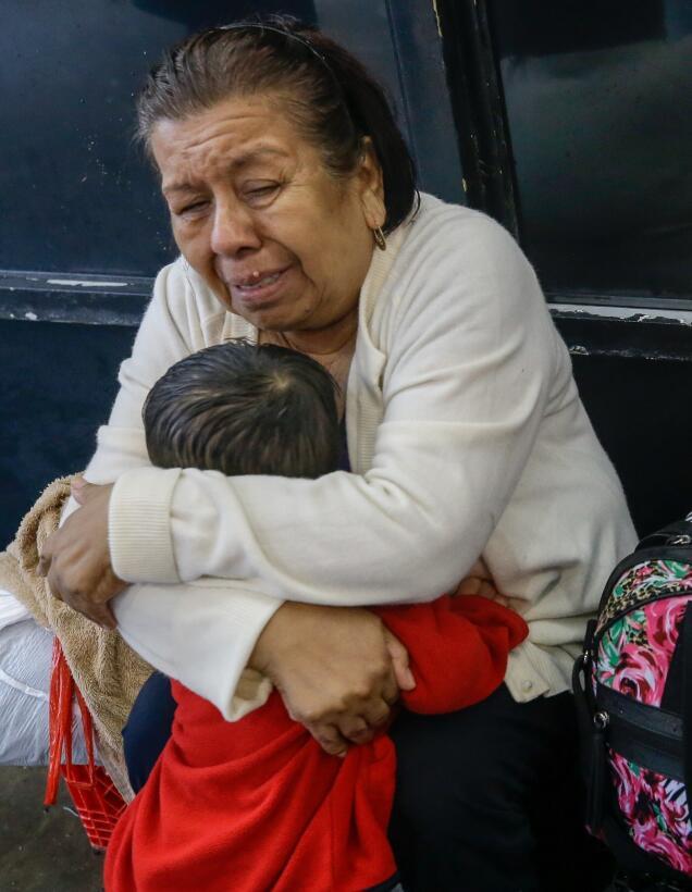 La residente Neri Sánchez y su nieto se abrazan en un bote de rescate do...