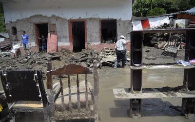 People try to save their belongings after a landslide in Salgar municipa...