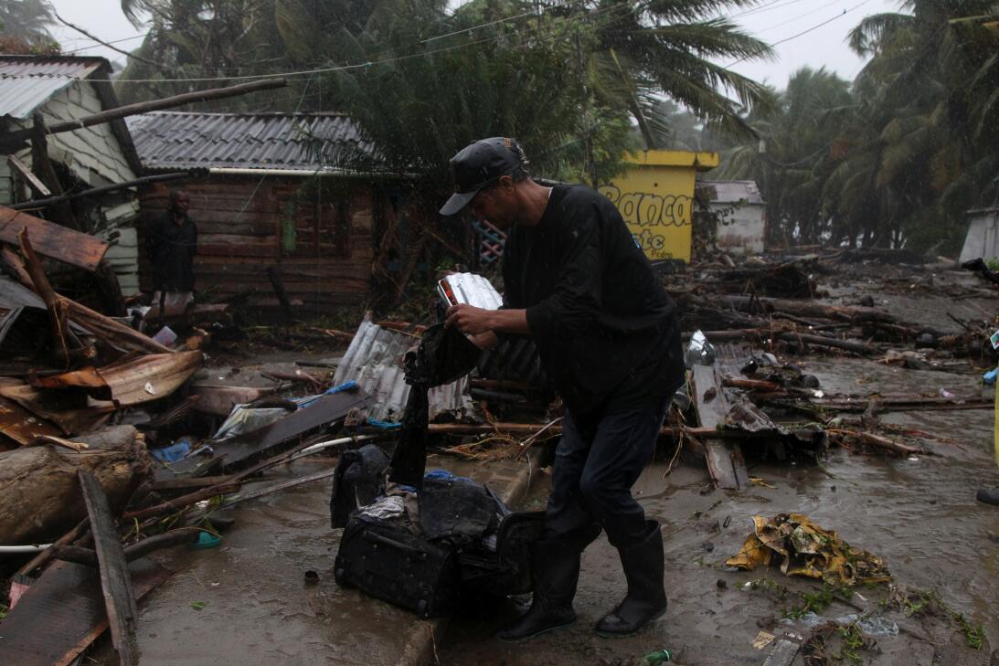Un hombre empaca algo de ropa que recuperó de su hogar afectado por el p...
