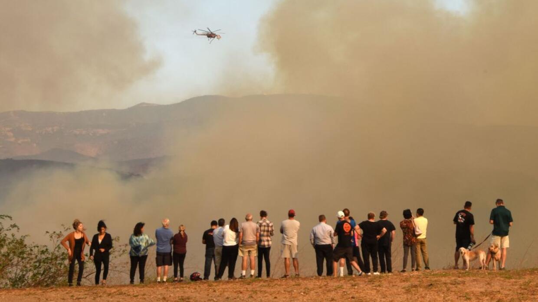 Un grupo de personas mira los esfuerzos de bomberos por controlar el inc...