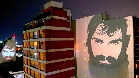 Santiago Maldonado's face reflected on apartment buildings in Buenos Aires.