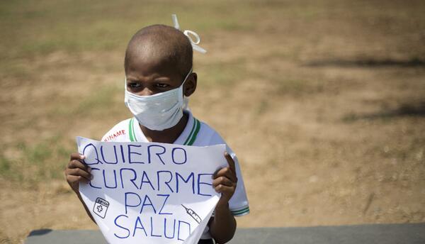 Oliver Sánchez, de 8 años, sostiene un cartel durante una protesta contr...