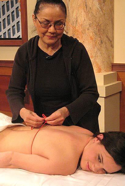 Una mujer muestra como trabajan las masajistas.