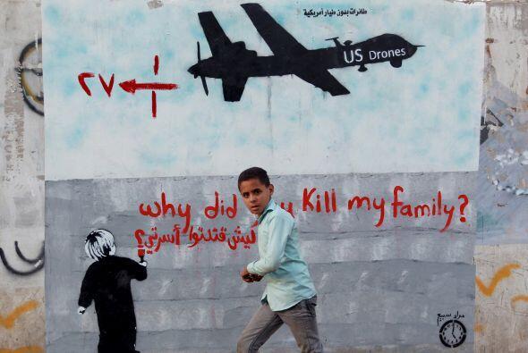 Un niño yemení pasa frente a un mural que muestra a un dron estadouniden...