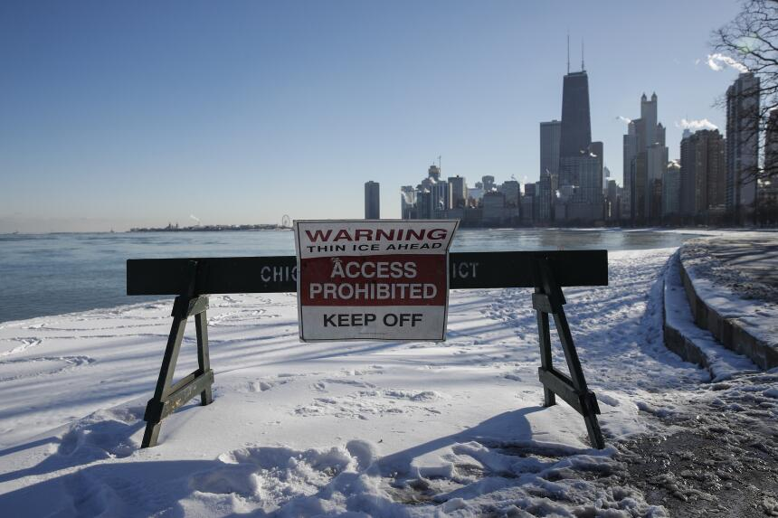 Una señal advierte a los peatones a lo largo de la orilla del lago. Las...