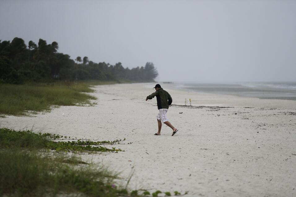 A beachgoer runs off the beach as the early effects of Hurricane Irma pi...
