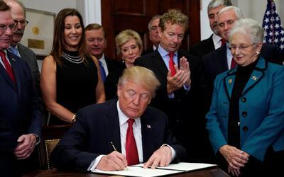 El senador Rand Paul de Kentucky aplaude a Donald Trump mientras firma s...
